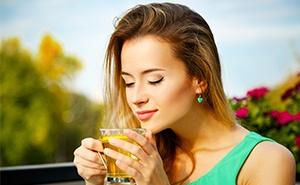 donna con canotta azzurro che beve infuso caldo