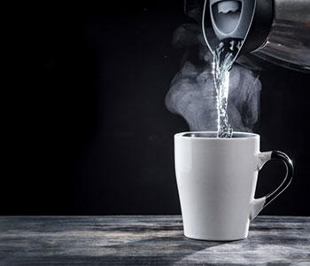 thermos con acqua calda che viene versata in tazza bianca