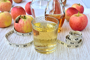 Apple cider vinegar diluted with water, slimming drink in a glass, ripe apples, measuring tape in inches, on a table.