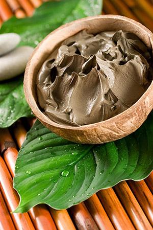 impacchi di argilla in ciotola marrone su foglie verdi