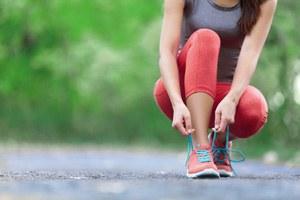 donna in tuta da ginnastica che si allaccia le scarpe