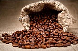 chicchi di caffè arabica marroni che si spandono da un sacco di iuta marrona