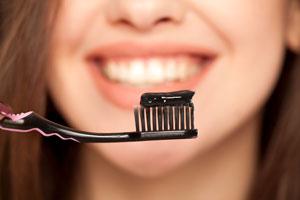 Uno spazzolino nero con dentifricio al carbone attivo e sullo sfondo una faccia sfocata con un sorriso