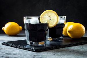 Due bicchieri di limonata carbone attivo su una fetta nera con 2 limoni accanto