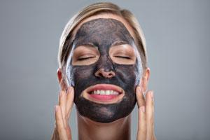 Una donna sorridente con una maschera di carbone attivo