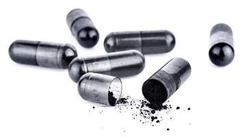 pillole nere di carbone vegetale aperte che ece polvere nera