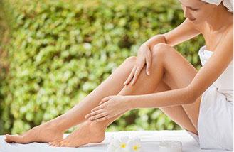 donna in accappatoio che si massaggia le gambe per aumentare circolazione