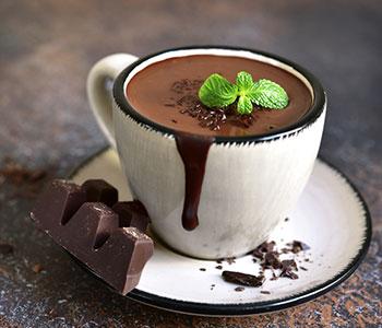 cioccolata fondente calda in tazza bianca con foglia di menta sopra e ttavoletta di cioccolata accanto