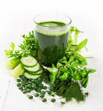 bicchiere di frullato verde clorella in mezzo a verdura verde e capsule verdi di clorella