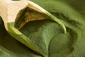 polvere verde di clorella su un cucchiaio marrone di legno