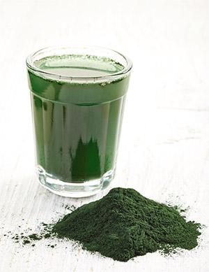 bicchiere di frullato verde di clorella vicino a polvere verde
