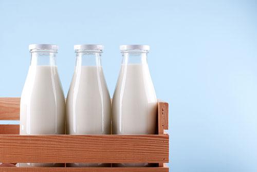 3 bottiglie di latte di vetro dentro una cassa di legno su fondo blu