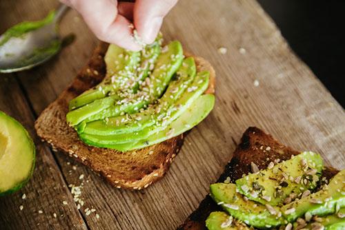 Mettere a mano i cereali nel pane integrale con fette di avocado