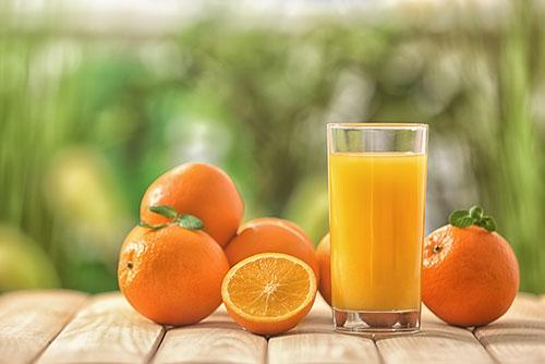 Succo d'arancia in un bicchiere di vetro e frutta arancione intorno