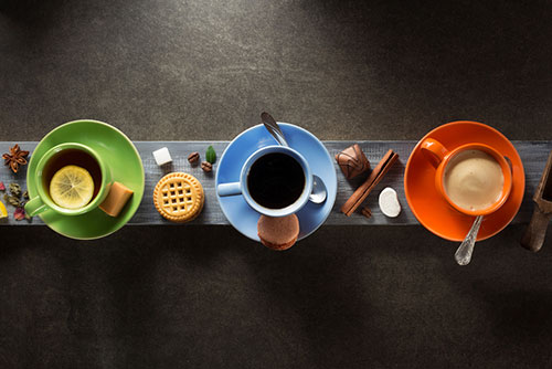 Tazza verde con il tè blu della tazza con il caffè arancio della tazza con latte e i biscotti intorno