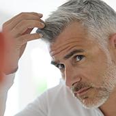 uomo con capelli brizzolati che si tocca la testa e i capelli