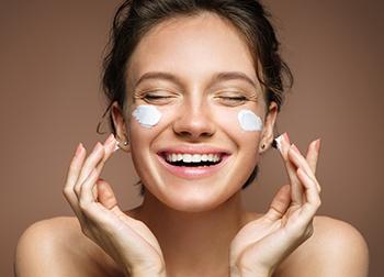 donna in bagno che si mette crema bianca sul viso e sorride