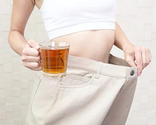 infuso di te giallo in tazza trasparente e donna che apre circonferenza pantaloni