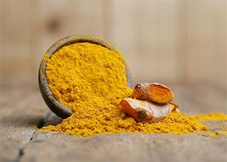 polvere di curcumina gialla arancione in ciotola su tavolo
