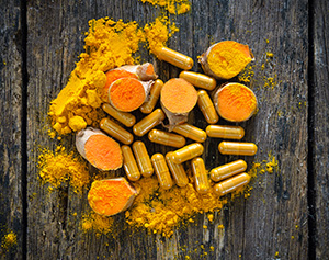polvere arancione in ciotole e capsule di curcuma su tavolo marrone