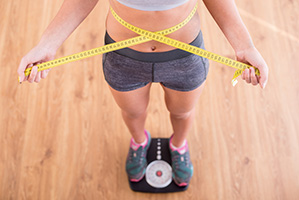 donna in piedi su bilancia con metro giallo sulla pancia