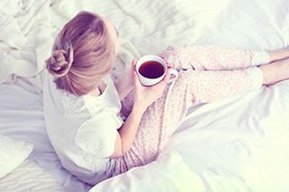 donna che beve infuso caldo seduta sul letto in pigiama