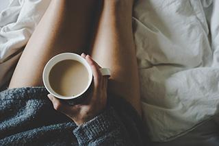 donna con maglione nero che beve infuso caldo seduta sul letto in pigiama