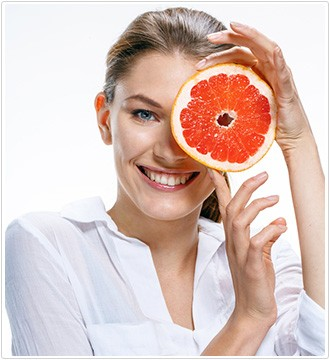 donna con camicia bianca e una fetta di arancia davanti alla faccia