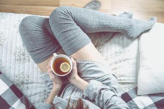 donna che beve infuso caldo seduta sul divano in pigiama
