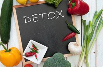 detox scritto su lavagna nera in mezzo a frutta e verdura fresca
