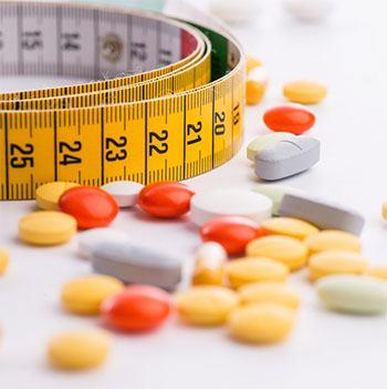pillole capsule e compresse dimagranti e un metro giallo