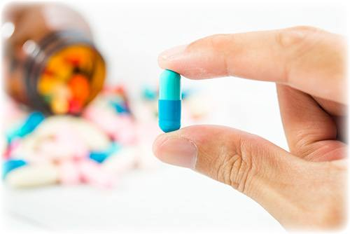 mano di uomo che tiene pillola blu tra le dita e ha altre pillole sullo sfondo