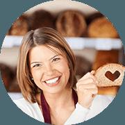donna che sorride mostrando un pezzo di pane con un cuore dentro