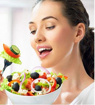 donna che mangia insalata di verdura fresca in una ciotola