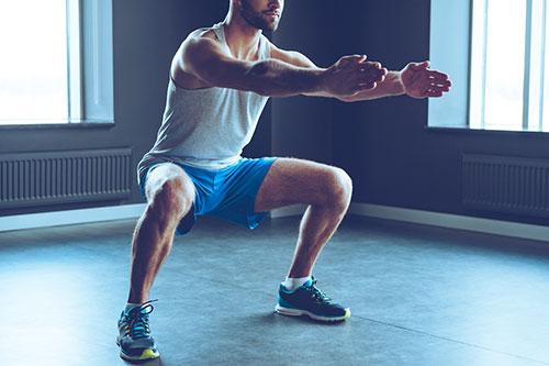 uomo in palestra facendo squat con le braccia tese