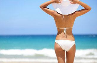 donna in costume in spiaggia ocn cappello e costume bianco