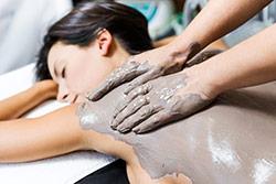 donna in spa che si fa fare un massaggio con fanghi di argilla