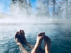 coppia alla spa con piedi nell'acqua e bosco attorno