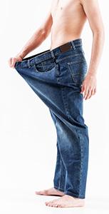 uomo che misura chili persi allargando la cinta dei pantaloni