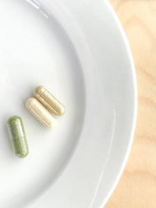 piatto bianco con tre pillole bianca verde gialla su tavolo