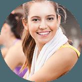 donna che ride in palestra con asciugamano bianco al collo