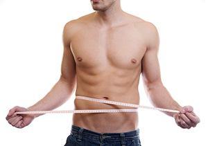uomo che si misura il girovita dopo aver perso chili