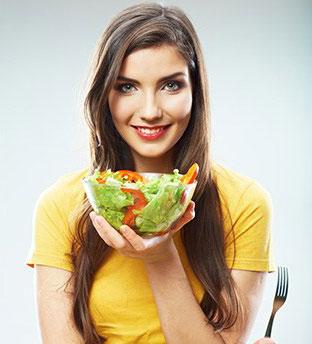 donna che sorride con un'insalata fresca in una mano