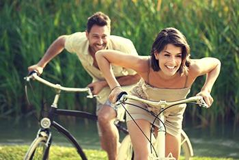 coppia di ragazzo e ragazza che corrono in bicicletta