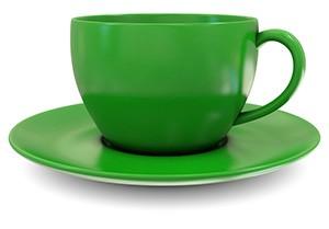 tazza verde che riposa su un piccolo piatto su uno sfondo bianco