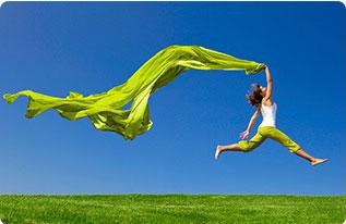 ragazza che salta su un prato verde con cielo azzuro