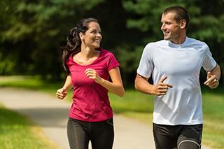 coppia di donna e uomo che corrono in un parco vicino ad alberi