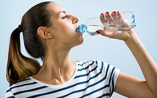 donna in pigiama che beve acqua da bottiglietta di plastica