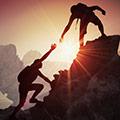 due ragazzi che si aiutano per scalare una montagna
