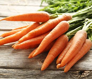 mucchio di carote fresche arancioni con foglie verdi su tavolo marrone